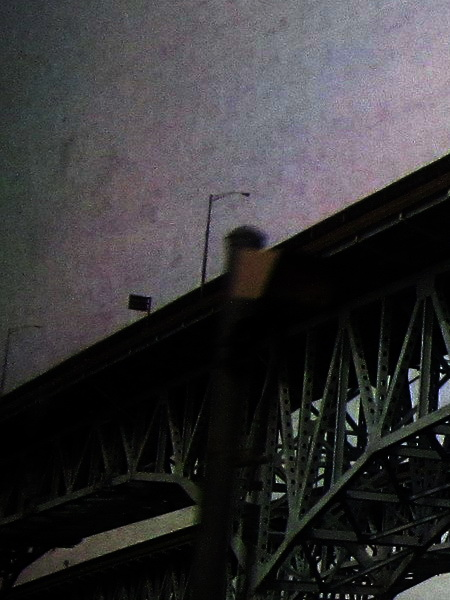 grainy image looking up at a slice of bridge