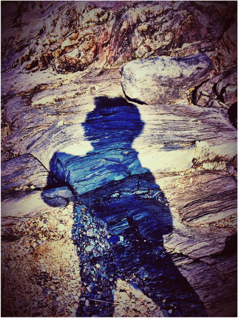 self portrait photo of author's shadow against rock and sand