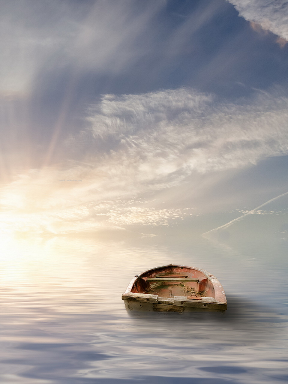 lone row boat in sea with rising sun and big sky