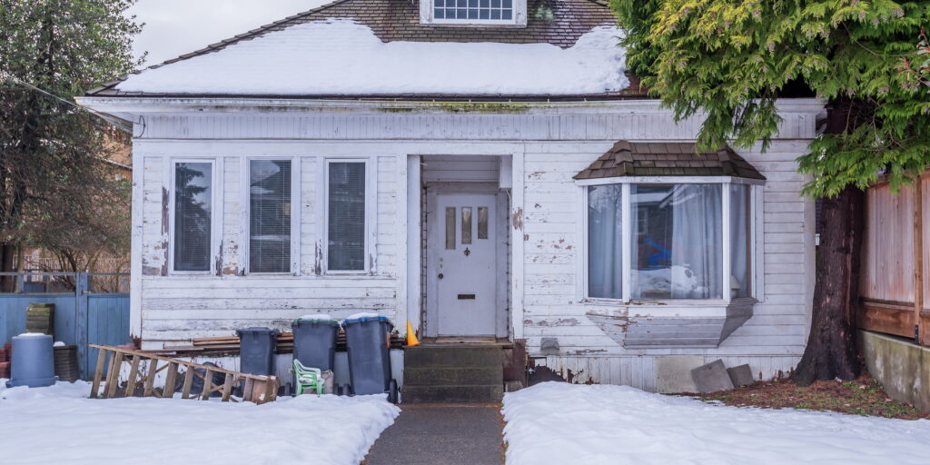 white run down bungalow with overflowing garbage cans in front