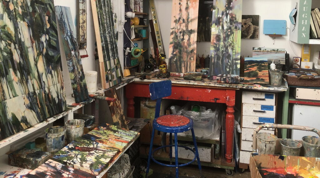 artist's studio with abstract apintings, paint palettes, masking tape, desk and chair