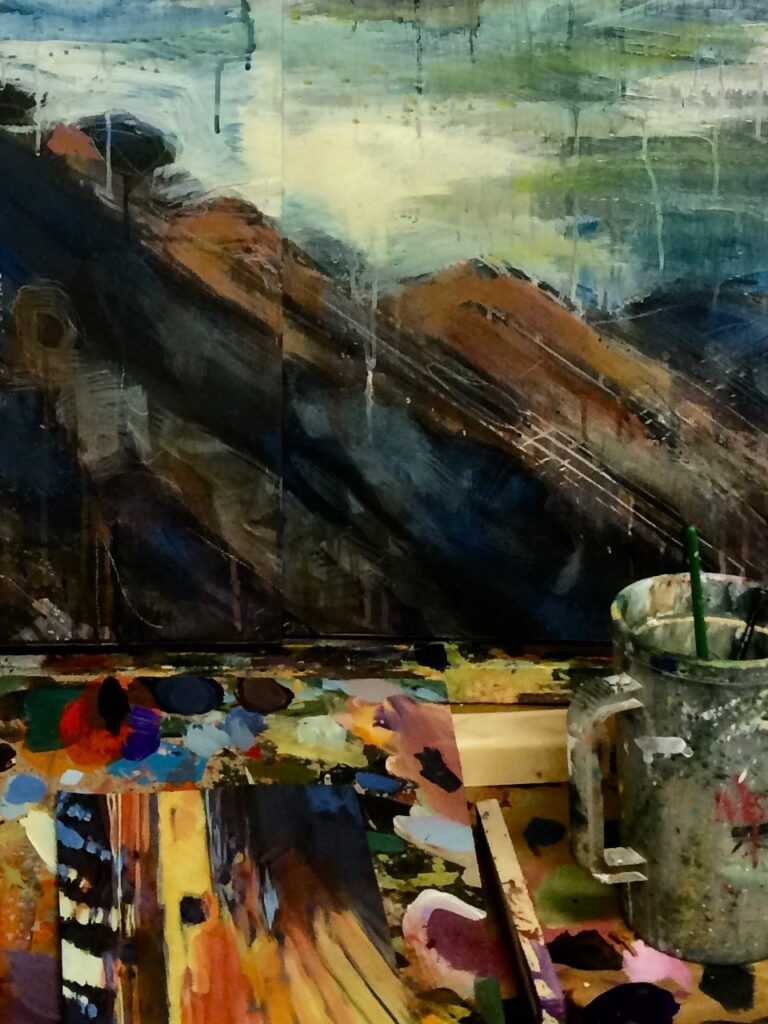 abstract landscape painting in progress with paint palette and paintbrushes