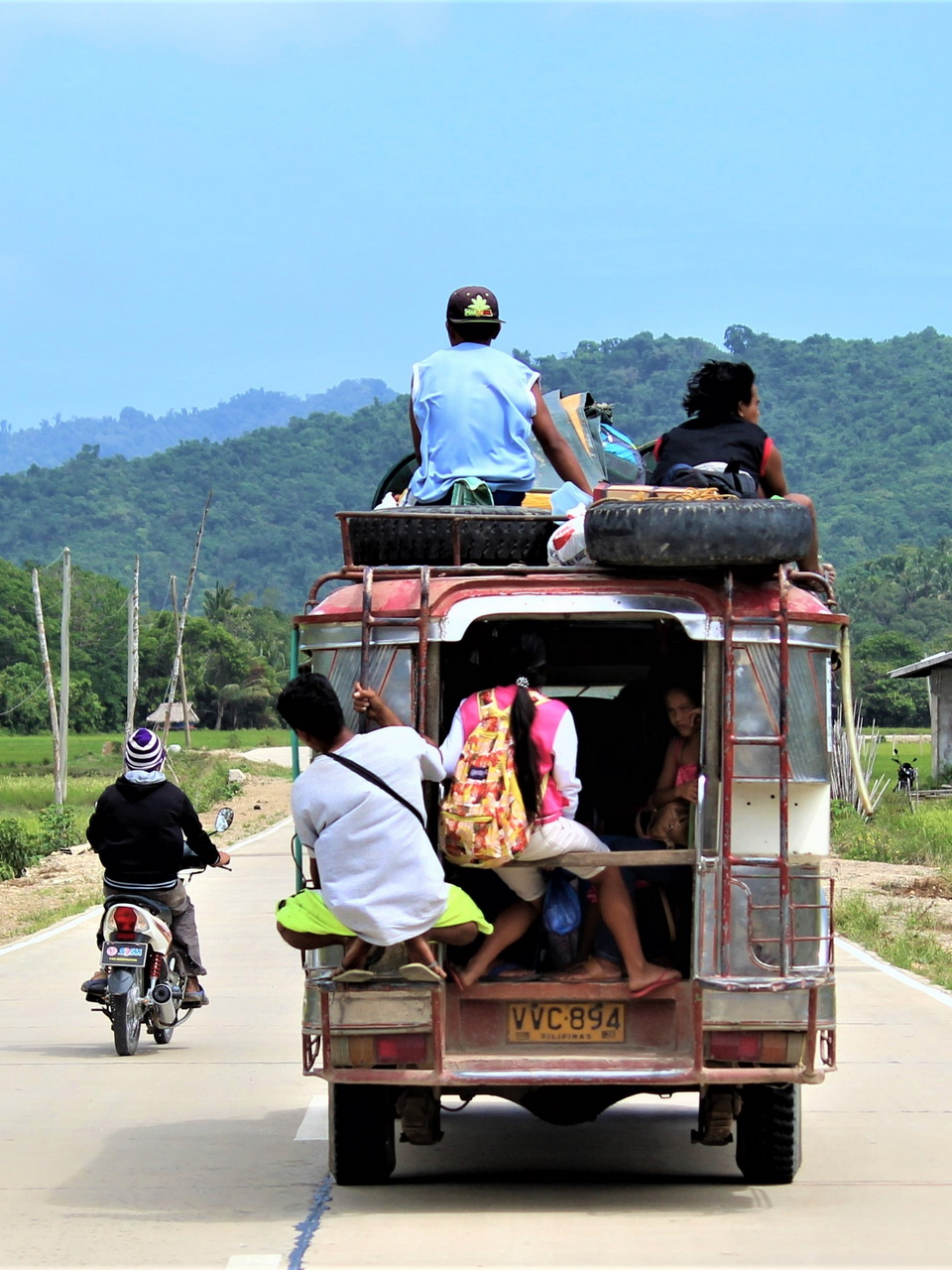 a small old bus full of people with two men sitting on top, a woman sitting at the back with the doors open and another man hanging onto the back. A man on a motorcycle is riding next to it on a small paved road toward tree-covered mountains