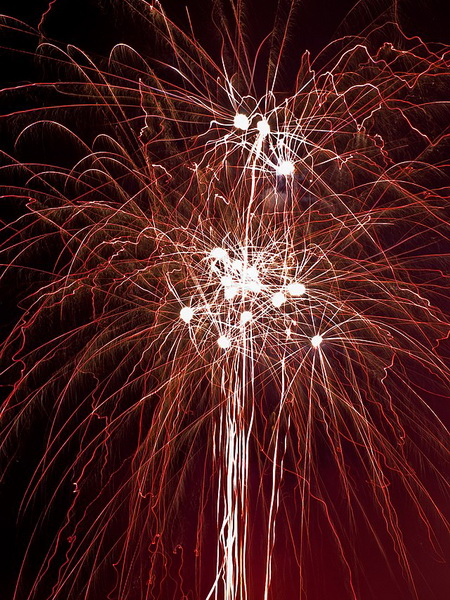 streams of red and gold fireworks falling in the dark sky with bright balls of gold light in the middle